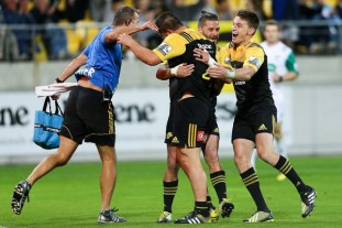 Beauden Barrett, Cory Jane and staff member Richard Wyatt congratulate Dane Coles after his try