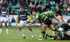 Northampton Saints scrum-half Kahn Fotuali'i throwing the ball against Bath Rugby and George Ford