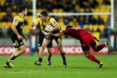 The Hurricanes playmaker Beauden Barrett is tackled by the Reds fullback Ayumu Goromaru