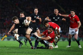 The New Zealand first-five eighth Beauden Barrett is tackled by the British & Irish Lions number 8 Taulupe Faletau in the first Test