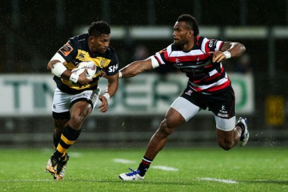 Waisake Naholo is running the ball for Taranaki as Tevita Nabura from the Counties Manukau is chasing him during the Mitre 10 Cup 2017