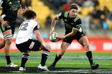 The Hurricanes playmaker Beauden Barrett passing the ball as the Sunwolves centre Michael Little tries to stop him during the Super Rugby 2018
