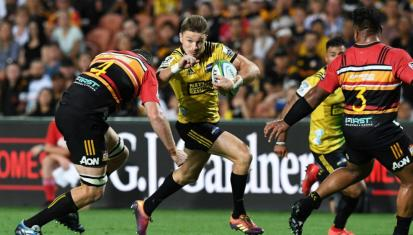 The Hurricanes pivot Beauden Barrett trying to avoid Chiefs' Brodie Retallick's tackle during the Super Rugby in 2019